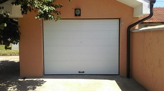 garažna vrata bele boje na narandžastoj fasadi